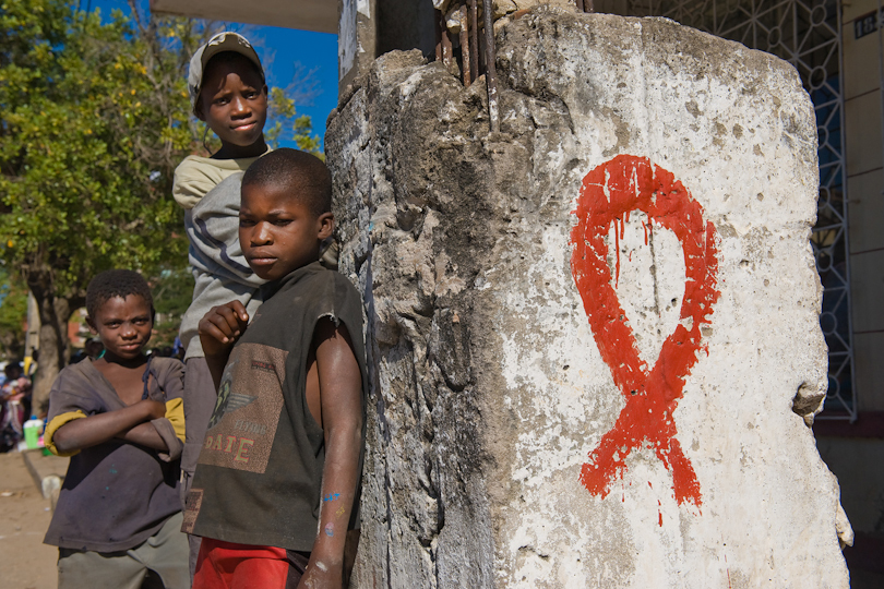 Street children standing at a pillar with a <p>painted HIV/AIDS ribbon, Quelimane Mozambique