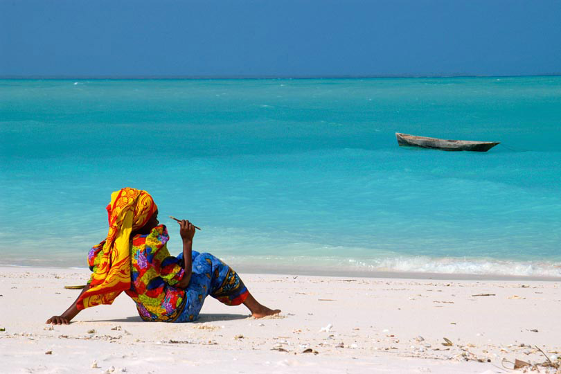 Woman in traditional dress rests <p>on the beach of Zanzibar